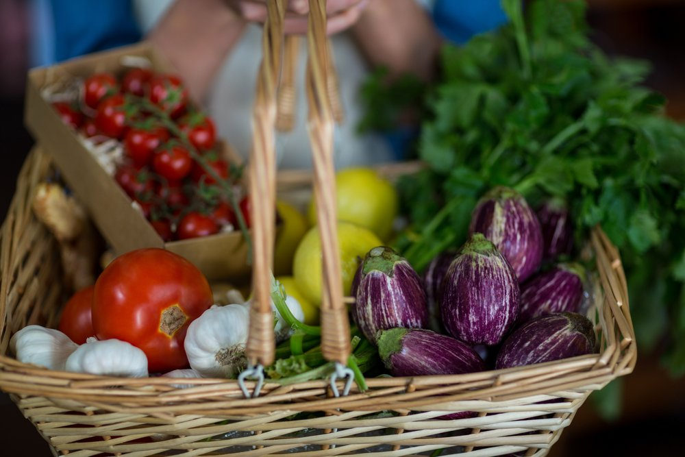 Close-up of female staff holding basket of vegetables in organic section of supermarket-2