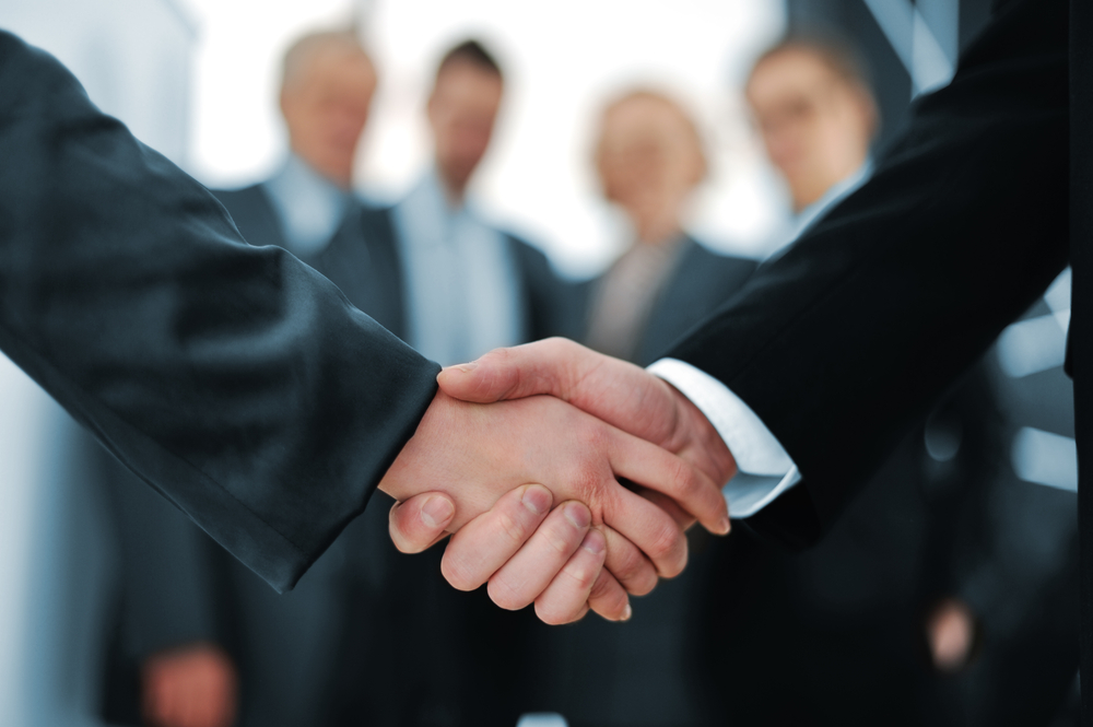 Handshake in front of business people-1